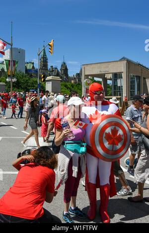 Ottawa, Kanada - Juli 2019: Frau posiert für Bild mit Mann in einem kanadischen Superhelden Outfit gekleidet während der jährlichen Canada Day Feier in der Ca - Stockfoto