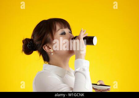 Asiatische Frau Trinken aus der Tasse Espresso - Stockfoto