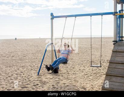 Ältere Frau genießen den Ruhestand leben Gefühl glücklich und gesund Spaß Schwingen auf einer Schaukel im Strand in einen sonnigen schönen Tag. Im aktiven Alten pe - Stockfoto