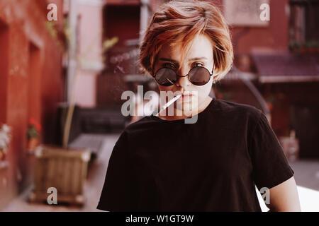 Tausendjährige cool hübsches Mädchen mit kurzen roten Haaren und Spiegel Sonnenbrille rauchen Zigarette in die alte Stadt mit roten Wänden - Stockfoto