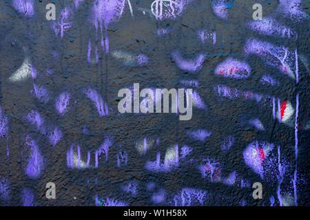 Fragment der schmutzig und voller Flecken an der Wand mit alten abgeplatzte Farbe mit violetten Farben, Scratch, grunge Textur close-up. Modernen abstrakten Hintergrund