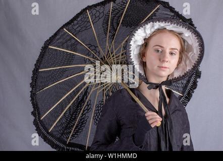 Viktorianische Frau in Schwarz Ensemble, Sonnenschirm und Schal - Stockfoto