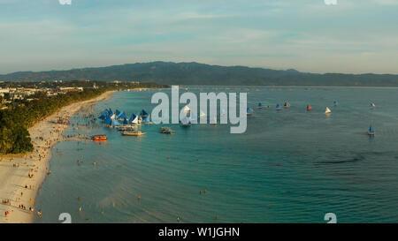White Beach auf der Insel Boracay mit Touristen und Segeln Boote bei Sonnenuntergang, Ansicht von oben. Tropischen Strand mit Segelboot. Sommer und Reisen Urlaub Konzept. - Stockfoto