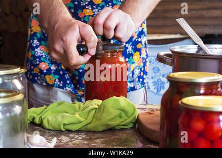 Der Mann schließt mit Gläsern eingelegte Tomaten und einer Sauce aus Mehl in eine rustikale Küche im Sommer - Stockfoto