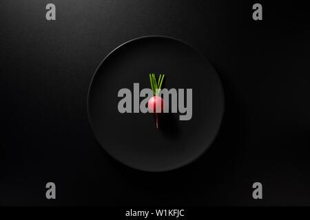 Ein rettich oder Kohlrabi in schwarz Platte auf Moody schwarzen Hintergrund serviert. Ansicht von oben. Gesunde Ernährung Konzept. - Stockfoto