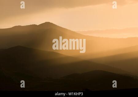 Die Sonne über dem Wasatch Mountains auf einem dunstigen Abend in Silver Creek in der Nähe von Park City, Utah. - Stockfoto