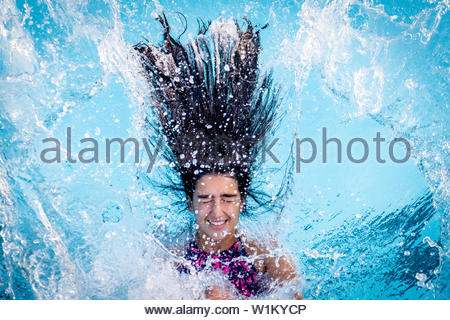 Junge brunette Mädchen fällt rückwärts in einen Pool - Stockfoto
