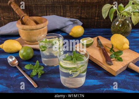 Mojito Cocktail auf einer blauen Tabelle mit Pfefferminz, Zitrone und Limette Zutaten - Stockfoto