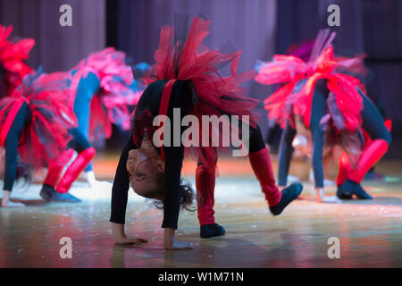 Indikative Ausbildung Zirkusschule. Kleine Mädchen führen Sie einen Tanz. Tanz für helovinna in rot Kostüme. Kleines Mädchen d - Stockfoto