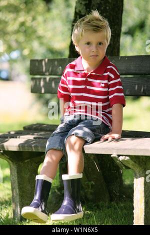 Junge (4-5 Jahre) auf einer Bank sitzen, Steiermark, Österreich - Stockfoto