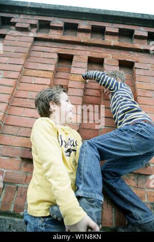 Junge, Freund eines Bunk-up über eine Wand - Stockfoto