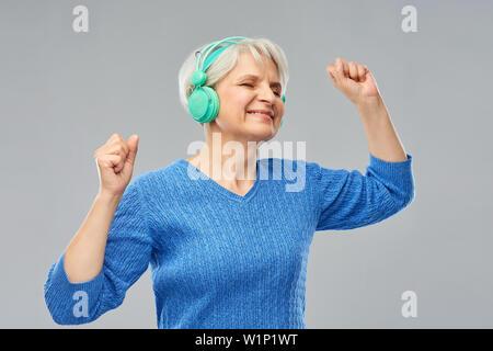 Ältere Frau in Kopfhörer Musik hören - Stockfoto