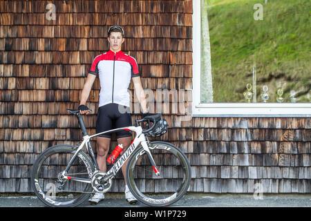 Junger Mann stehend an der Wand neben seinem Rennrad auf die Kitzbühler Alpen, Kitzbühlerhorn, Tirol, Österreich - Stockfoto