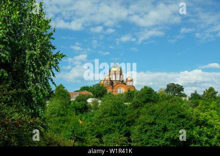 Orthodoxe Kirche auf einem Hügel. Christian traditionelle Tempel auf dem Hintergrund von Cloud blauer Himmel und grünen Wald Bäume am sonnigen Sommertag. Architektur und n - Stockfoto
