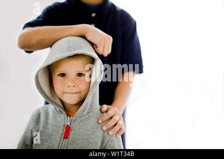 Porträt eines Jungen, der vor seinem älteren Bruder. - Stockfoto