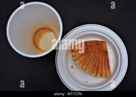 Ansicht von oben auf eine leere Tasse Kaffee und Muffin wrapper auf einem Papier Platte - Stockfoto