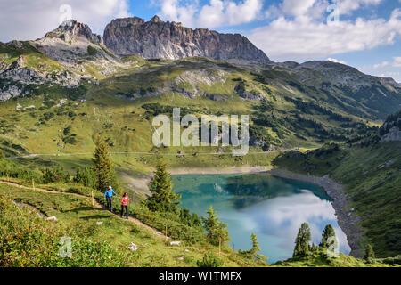 Ein Mann und eine Frau wandern über den Salvar Insee, rote Wand im Hintergrund, lechweg, Lech Quelle Berge, Vorarlberg, Österreich - Stockfoto