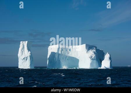 Ein Eisberg, einst viel größeren, aber jetzt mit drei Türmen, schwimmt im Meer, in der Nähe der South Shetland Inseln, Antarktis - Stockfoto