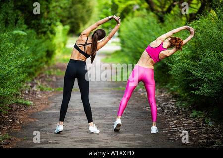 Zwei Frauen trainieren in den Park. Junge schöne Frau Übungen gemeinsam im Freien - Stockfoto