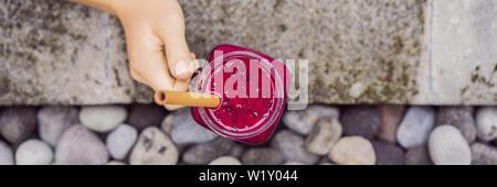 Junge Frau trinkt Dragon Fruit Smoothies auf dem Hintergrund der Pool. Fruit Smoothie - gesunde ernährung Konzept. Nahaufnahme von detox Smoothie mit - Stockfoto