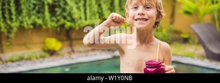 Cute boy Holding eine Flasche Dragon Fruit Smoothie oder Saft biegt seine Muskeln und lächelnd Banner, LANGE FORMAT - Stockfoto
