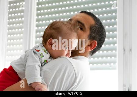 Vater Holding, die Krankenpflege küssen parenting kümmert sich um Baby Sohn Tochter sehr jung vor kurzem geboren neugeborene Kind Portrait auf der Suche vor - Stockfoto