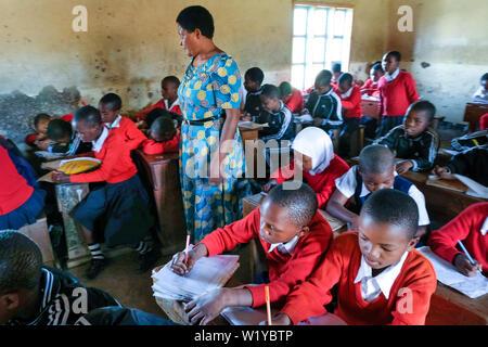 Lehrer und Schüler in roten Schuluniformen in eine Schulklasse der Grundschule Mwenge in Mbeya, Tansania