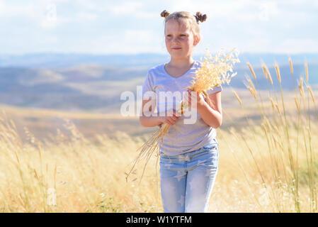 Gerne kleine Mädchen zu Fuß in goldenen Weizen, die Spikes von Weizen und Ohren von Hafer. Natur Schönheit, blauer Himmel, weiße Wolken und Feld von Weizen.