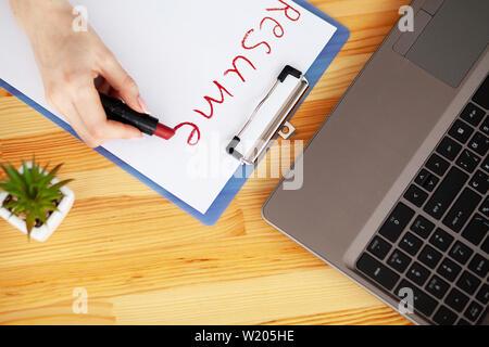 Job suchen. Weibliche Hand schreibt mit Lippenstift auf weißem Blatt Papier aufnehmen. Holz- Schreibtisch mit Laptop, Smartphone und Zubehör - Stockfoto