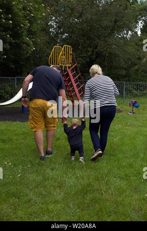 Kleinkinder lernen im Park mit Eltern zu Fuß - Stockfoto