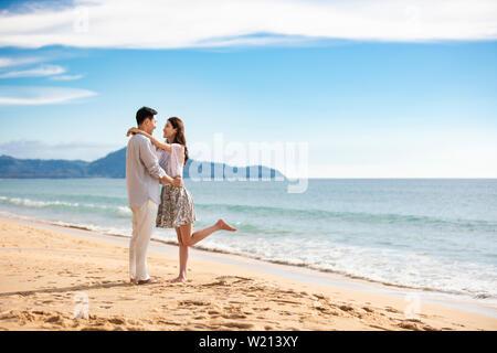 Glückliches junges Paar umarmt am Strand - Stockfoto