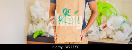 Mann mit einem Paket mit der Aufschrift GRÜN unter einem Haufen von Plastiktüten. Null Abfall Konzept. Das Konzept der World Environment Day BANNER, LANG - Stockfoto