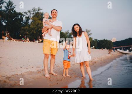 Blick auf Familie mit zwei Kleinkindern Kinder draußen am Fluss im Sommer. Glückliche junge Familie haben sie Spaß am Strand bei Sonnenuntergang. Aktive Eltern und Menschen - Stockfoto