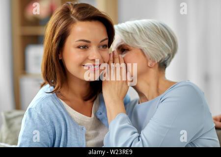 Ältere Mutter Flüstern zu erwachsenen Tochter zu Hause - Stockfoto