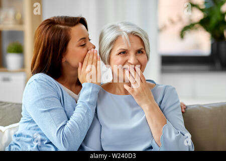 Erwachsene Tochter Flüstern zu den älteren Mutter zu Hause - Stockfoto