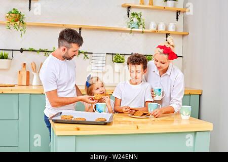 Familie Lächeln, das Frühstück in der Küche an einem sonnigen Tag - Stockfoto