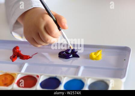 Handbemalt, Farben und Pinsel auf weißer Tisch. Mädchen Hände zeichnen mit Farben. - Stockfoto