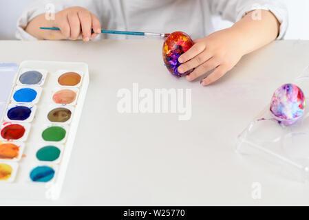 Kind Hände bemalte Ostereier, Farben und Pinsel auf weißer Tisch. Die Vorbereitung auf das Osterfest. Kid Hände zeichnen mit Farben. - Stockfoto
