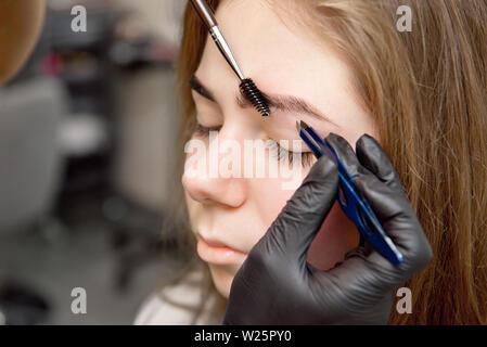 Schöne Frau Zeichnen einer Form der Augenbrauen mit kosmetischen Bürste. Make-up Artist Anwendung bis zu einem Modell - Stockfoto