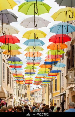 Novigrad, Istrien, Kroatien, Europa - 3. September 2017 - die Touristen zu Fuß durch eine Gasse mit bunten Sonnenschirmen oben - Stockfoto