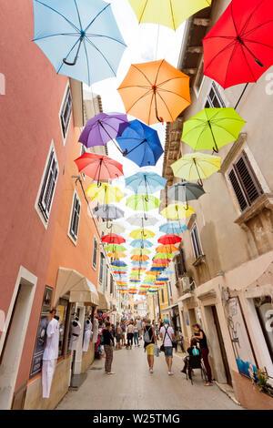 Novigrad, Istrien, Kroatien, Europa - 3. September 2017 - die Touristen zu Fuß durch die Altstadt von Novigrad mit Sonnenschirmen über Ihnen - Stockfoto