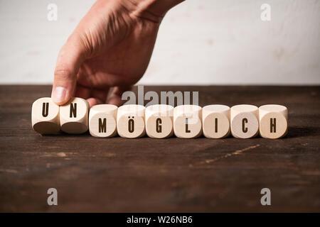 Unmögliches wird möglich (in deutscher Sprache) auf Holz- Hintergrund - Stockfoto