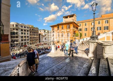 Ein paar Pausen auf der Spanischen Treppe in Rom, Italien, als Touristen vorbei, die Piazza di Spagna mit Touristen gefüllt mit Blick unten. - Stockfoto