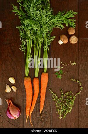 Frisch vom Bauernhof rohe Karotten mit Tops mit crimini Pilze, Knoblauchzehen, Schalotten, Oregano und Thymian Zweige auf dunklen Holzmöbeln im Landhausstil Hintergrund f