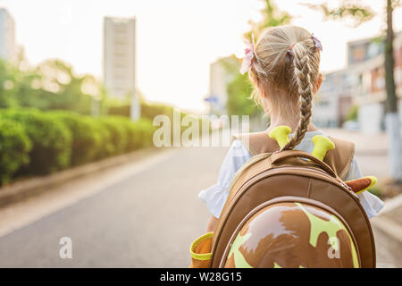 Kind Mädchen Schüler von hinten zu Fuß zurück zu Home nach dem Lernen Studie Schule alleine mit Schultasche, Vorschule und Kindergarten Bildung Konzept. Erste - Stockfoto