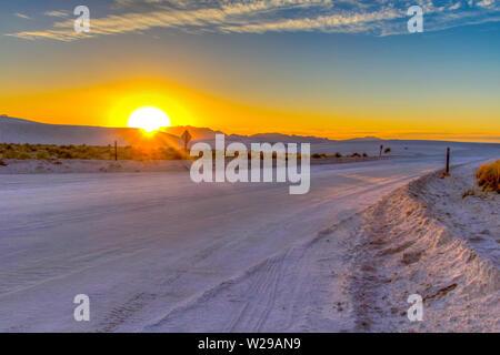Wüstenfahrt. Wunderschöner Sonnenuntergang in der Wüste mit abgelegenen Landstraßen, die sich durch die Sanddünen des White Sands National Monument in New Mexico schlängeln. - Stockfoto