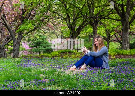 Junge Frau im Park sitzen an Ihrem Telefon. - Stockfoto