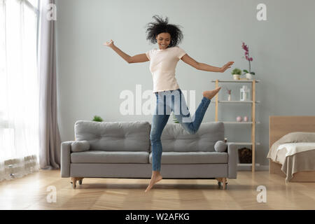 Unbeschwert fröhlichen afrikanisches Mädchen tanzen alleine zu Hause springen - Stockfoto