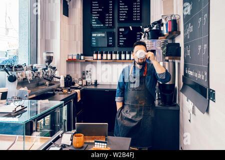 Kaukasischen jungen Mann barista Kaffee trinken aus der weißen Schale während seiner Mittagspause am Arbeitsplatz. Lustige authentische real life Moment der Small Business ow - Stockfoto