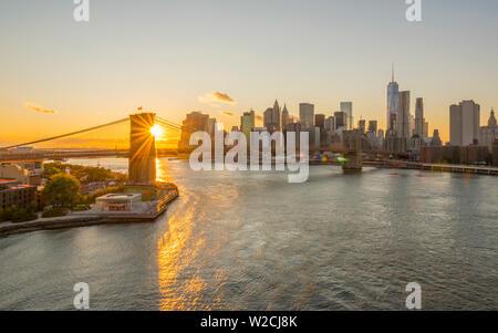 USA, New York, Skyline von Lower Manhattan und Brooklyn Bridge über den East River bei Sonnenuntergang - Stockfoto